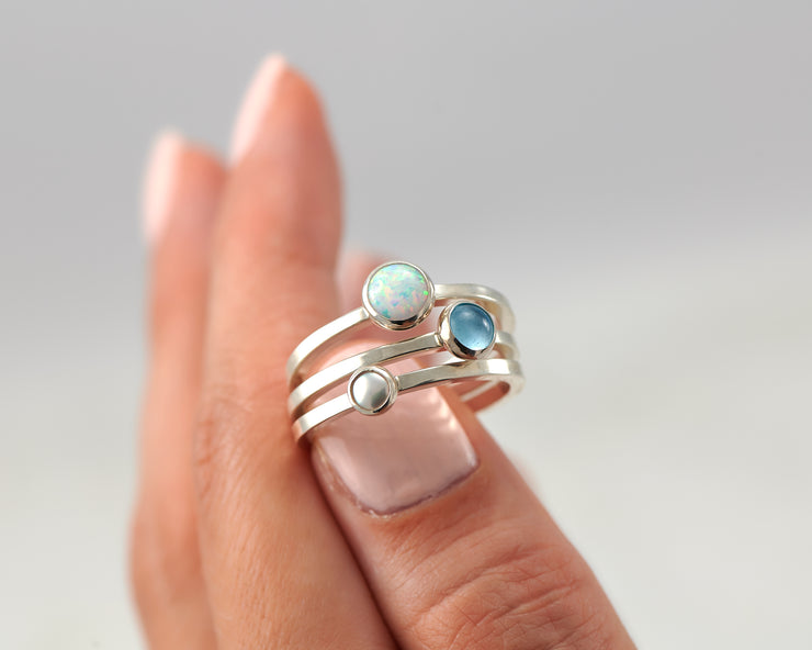 woman balancing silver stacking rings opal, pearl, blue topaz