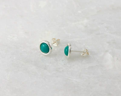 silver turquoise stud earrings on white marble