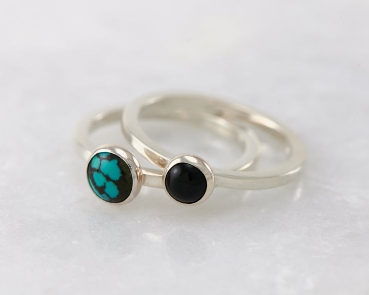 turquoise and black onyx silver stacking rings on white marble