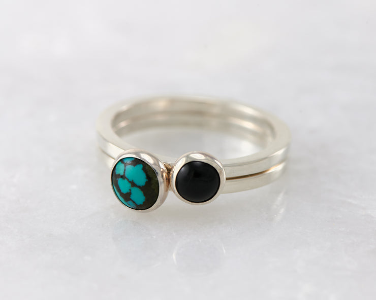 simple turquoise and black onyx silver stacking rings on white marble