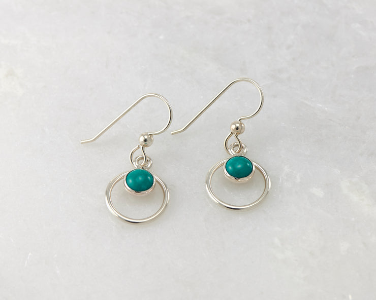 Silver polished turquoise hoop earrings on white marble
