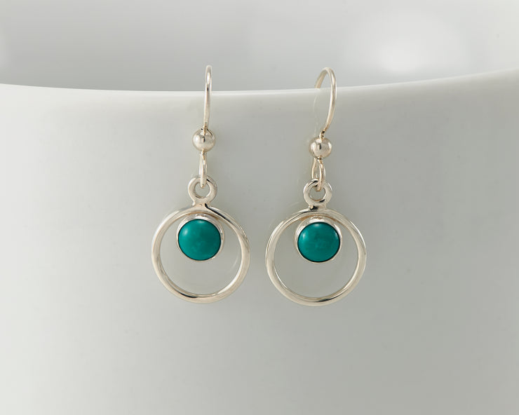 Silver turquoise hoop earrings on white cup