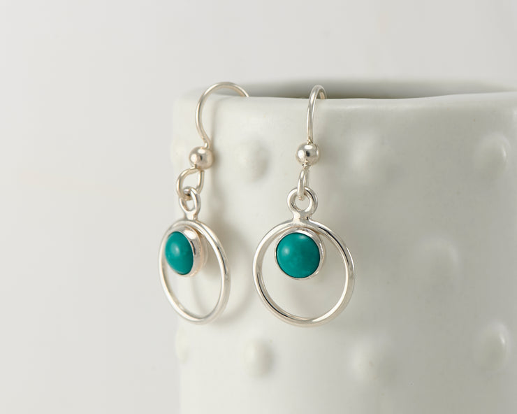 Silver polished turquoise hoop earrings on dotted vase