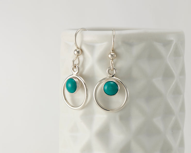 Silver turquoise hoop earrings on geometric vase