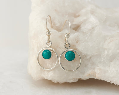 Silver turquoise hoop earrings on white rock