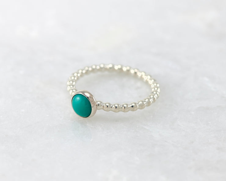 beaded turquoise ring on white marble