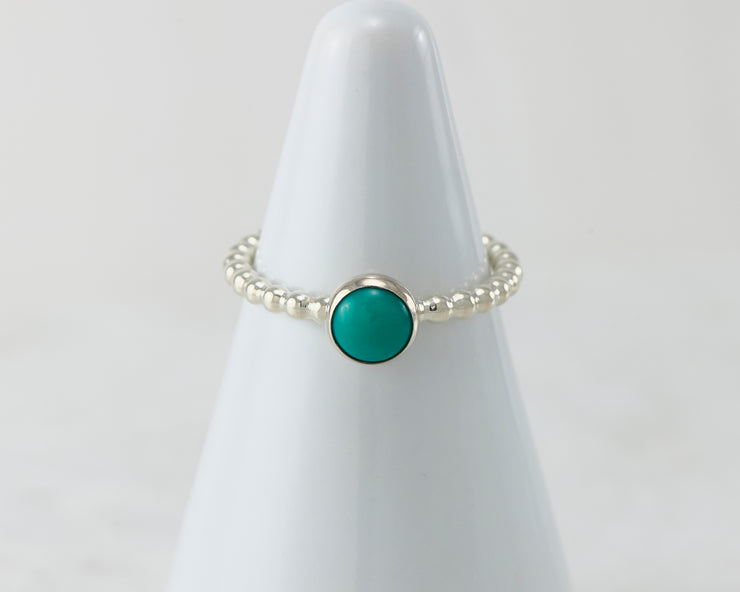 White ring holder with turquoise Silver ring