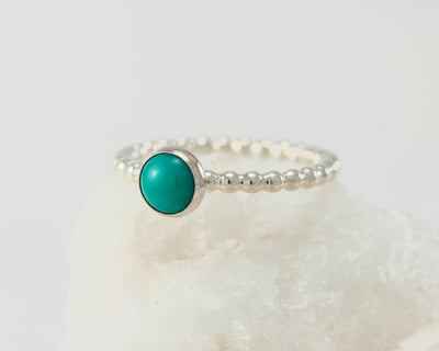 Silver turquoise beaded ring on white rock