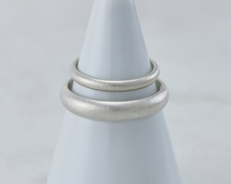 two brushed wedding bands on white ring holder