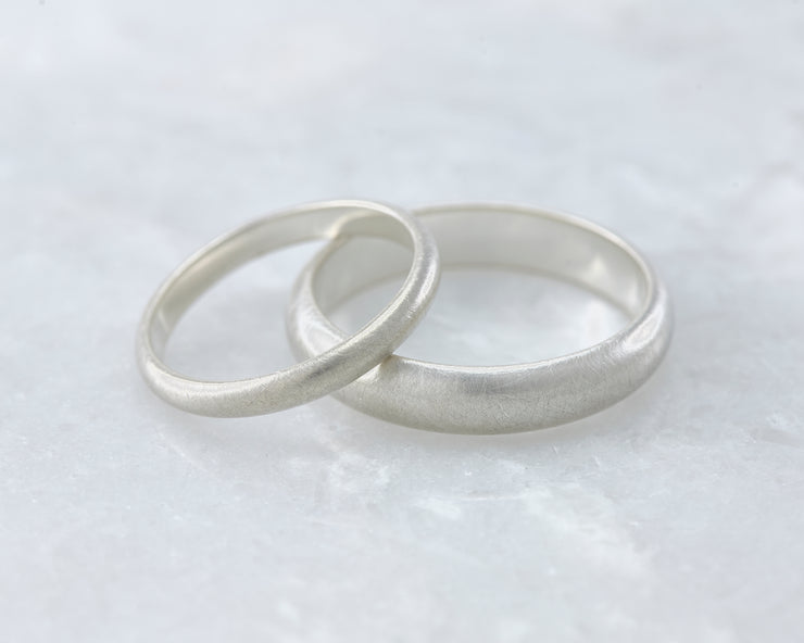 brushed wedding band set laying on white marble