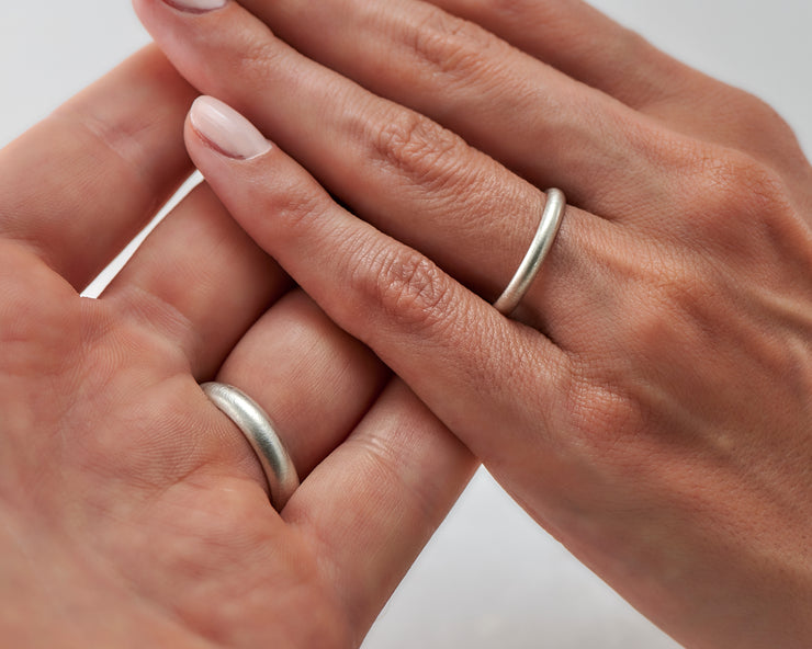 Man and woman holding hands wearing brushed wedding bands