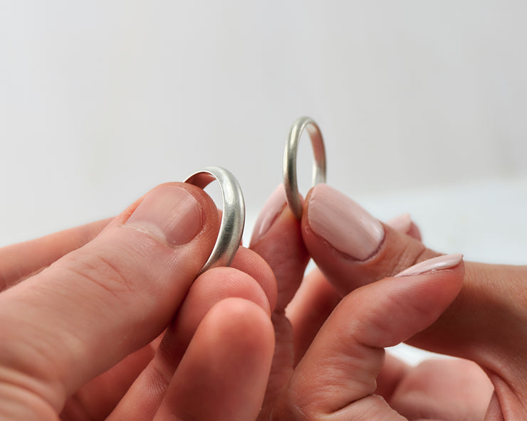his and hers brushed wedding bands on man and woman's hands