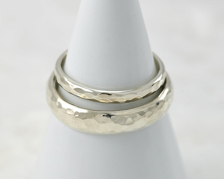 two hammered wedding rings on white ring holder