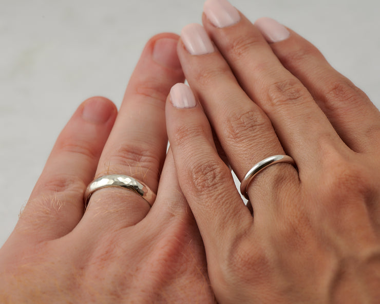 his and hers wedding bands on man and woman's hands