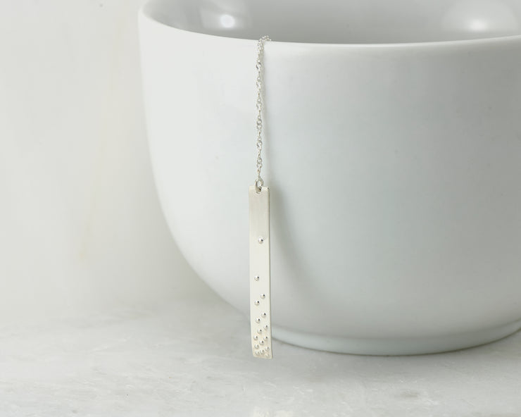 silver bar y-necklace on white cup