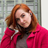 Flicka som bär JBuds Band Wireless Neckband Headset