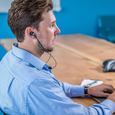 Man in Office Wearing Black Epic Executive Earbuds