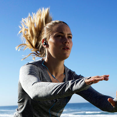 Woman Jumping Wearing Black and Blue Fit 2.0 Sport Earbuds