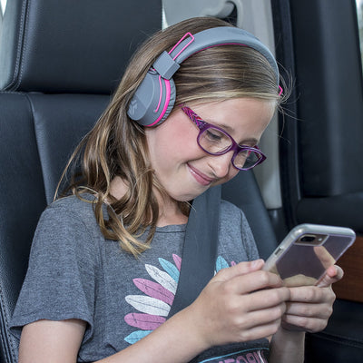 Bilde av jente som har på seg JBuddies Studio Bluetooth Over Ear Folding Kids-hodetelefoner i rosa