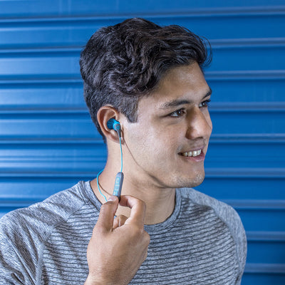 Guy draagt JBuds Pro Bluetooth Signature Earbuds in blauw