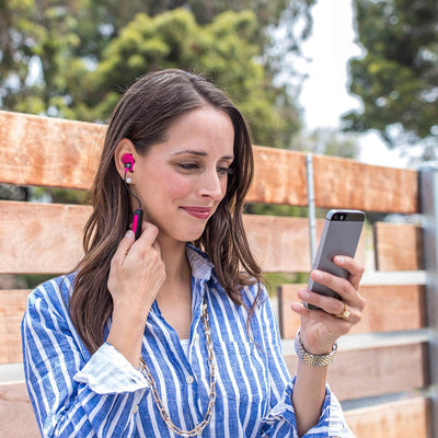 Chica vistiendo Metal Bluetooth Rugged Earbuds en rosa