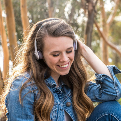 Flicka som bär Rewind Wireless Retro Headphones i vitt