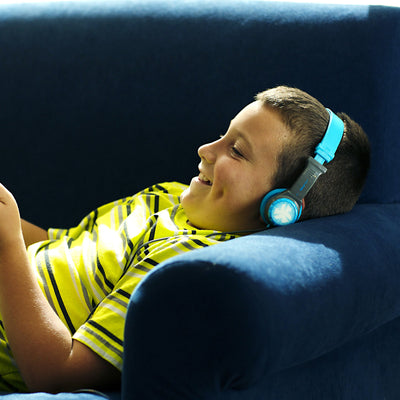 Boy Laying on Couch Wearing Blue and Gray JBuddies Headphones