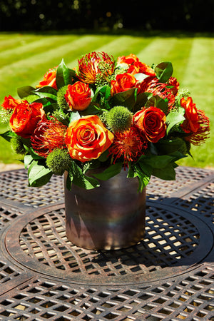 Roses, Dianthus and Skimmia in a Bronze Vase (orange)