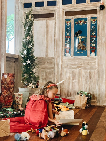 Girl squatting among presents next to Christmas tree