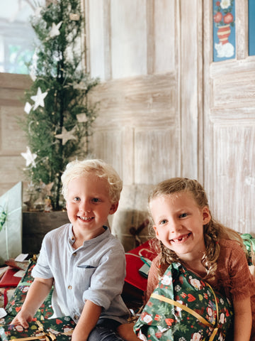 Children sitting with presents next to Christmas tree