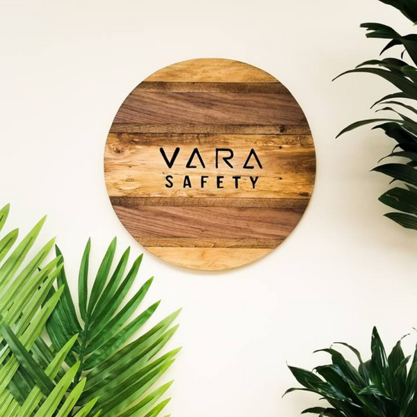 A wooden glazed sign with the Vara Safety named etched into the surface. There are bright green plants surrounding the sign.