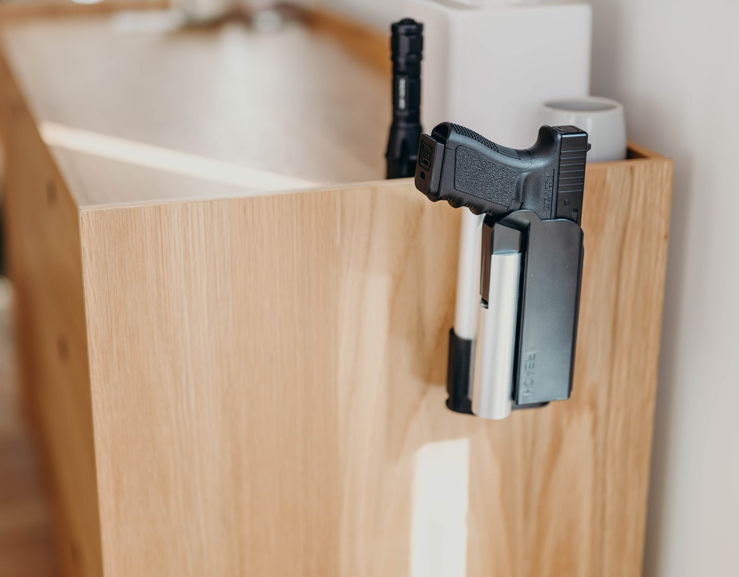 "Reach Holster Safe is seen attached to a brown credenza and a Glock handgun is locked in place. Text over image says, ""Fingerprint safe made for protection."""