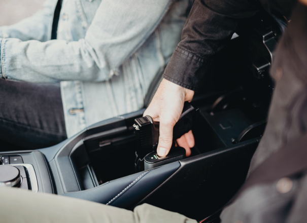 Reach Holster Safe is stationed in the center console of a vehicle. A woman sits in the passenger seat, while a man in the driver seat engages in stage 1 ready grip and presses their fingerprint on the biometric scanner.