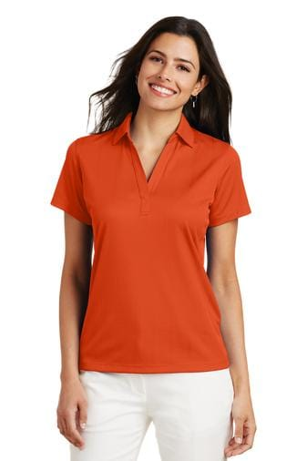 A front view of a woman wearing ladies Port Authority Performance Fine Jacquard orange polo shirt