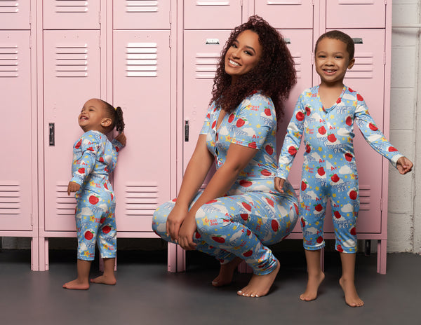 Image of a small toddler standing, with a curly haired adult woman squatting, with an older child standing on their tip-toes. The background is a line of pink lockers.