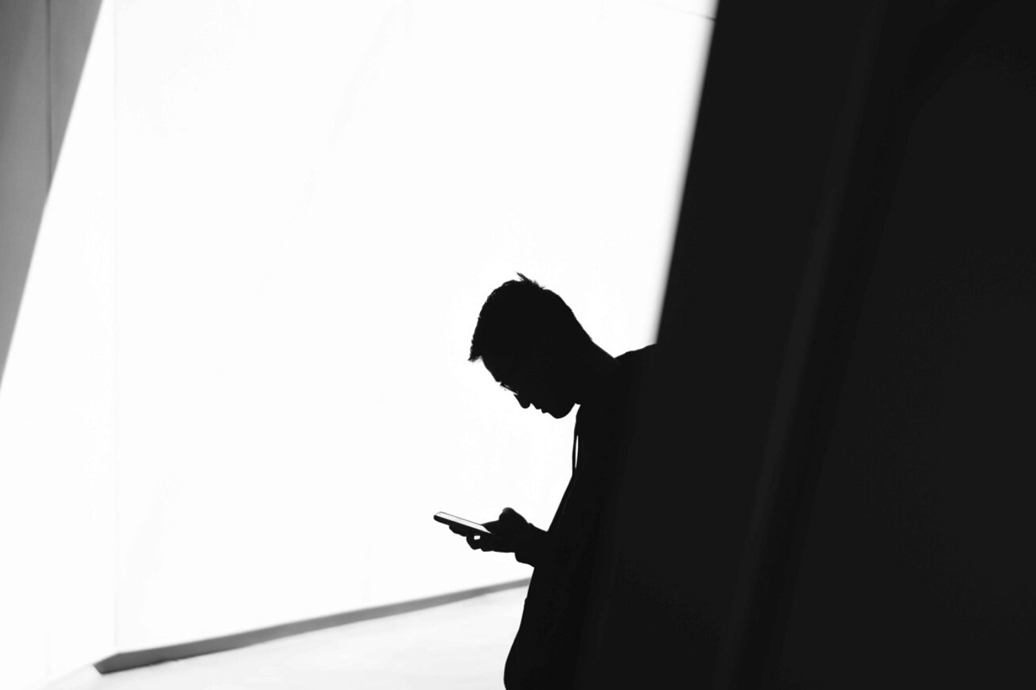 a man looking at his phone black and white