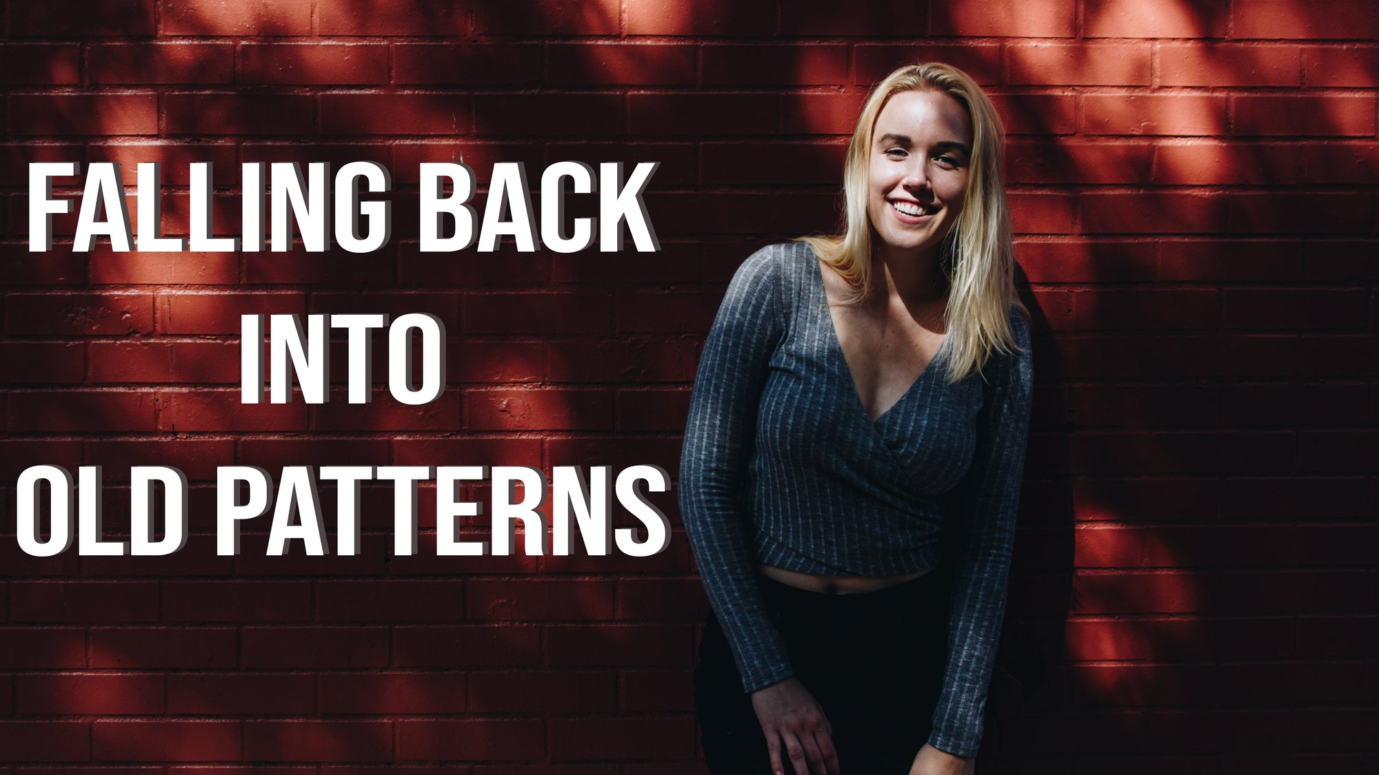 a blonde girl smiling against a red brick wall with text falling back into old patterns written