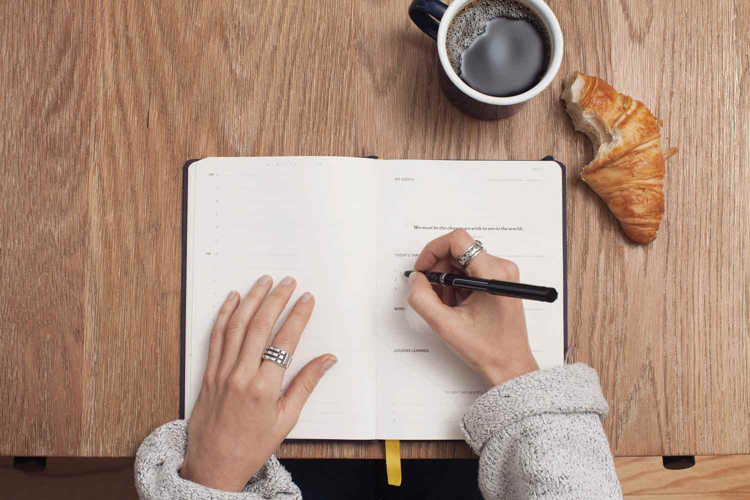a woman writing in a notebook with a cup of coffee and a croissant on the table
