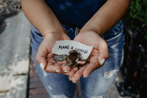 a woman holding change in her hands with a note that says make a change