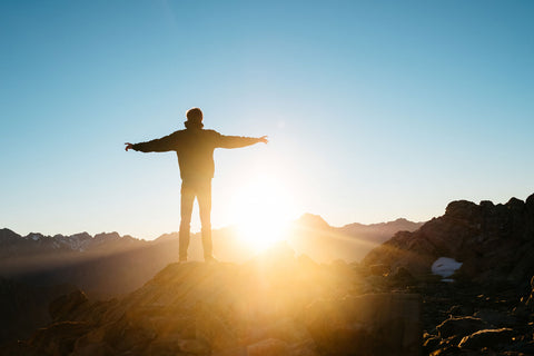 man standing on a cliff with open arms with the sun shinning