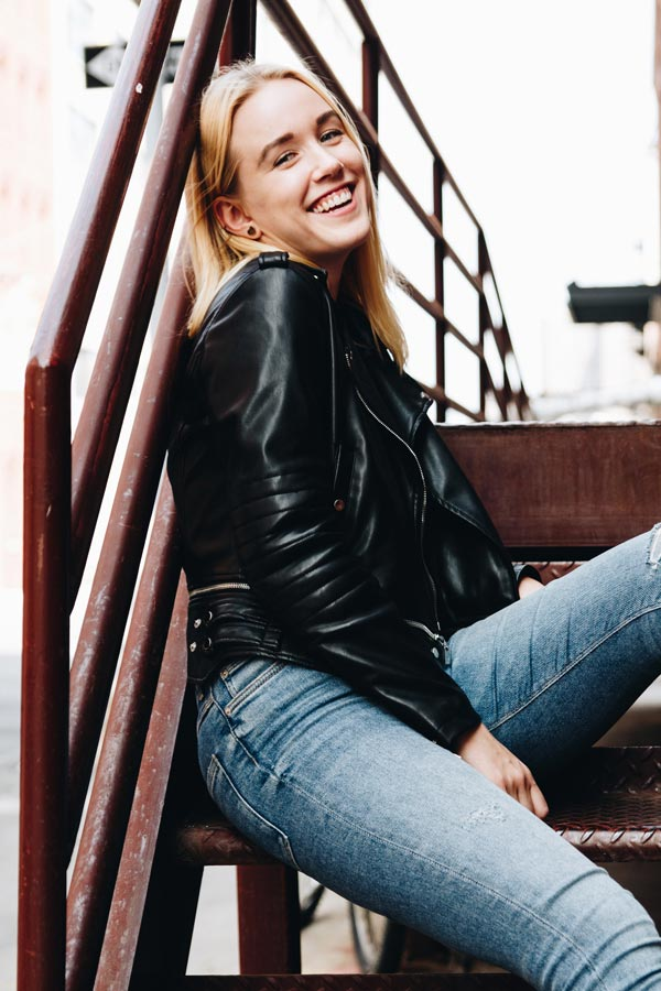 life coach online mindset coaching gabie rudyte siting on the stairs smiling in new york city