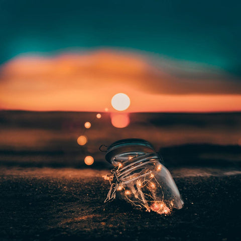 a jar in the sand with the sunset behind