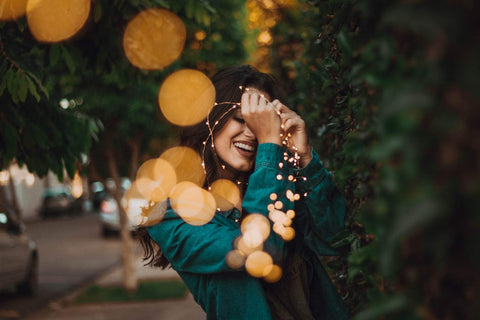 a woman smiling holding fairy lights