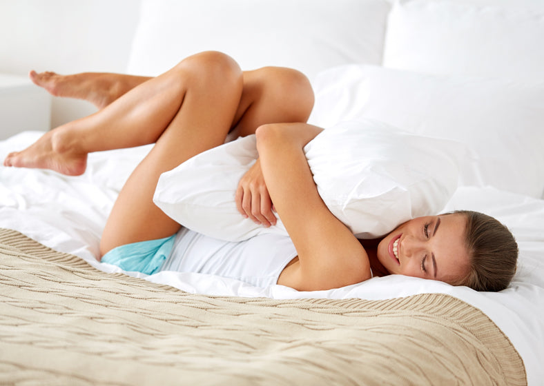 A woman feeling happy after finding the best pillow to sleep