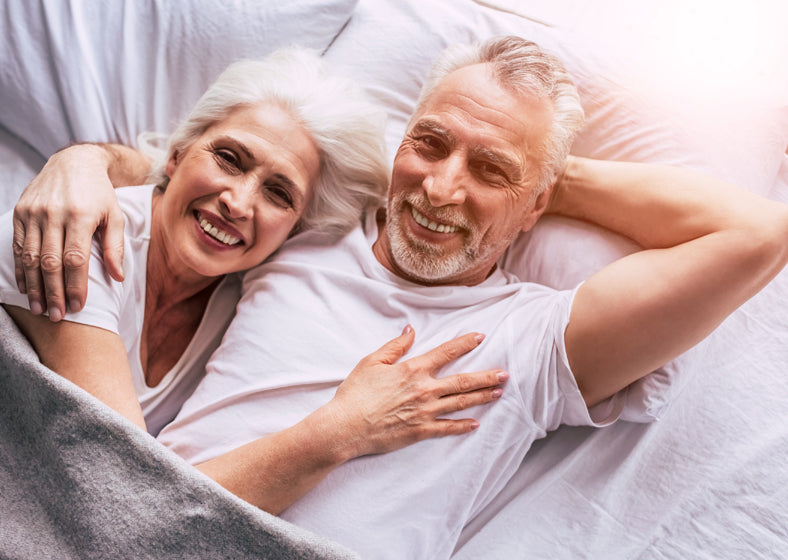Healthy smiling senior couple in bed