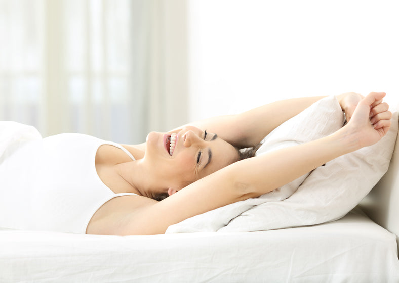 A woman waking up with a smile after sleeping on an organic latex mattress