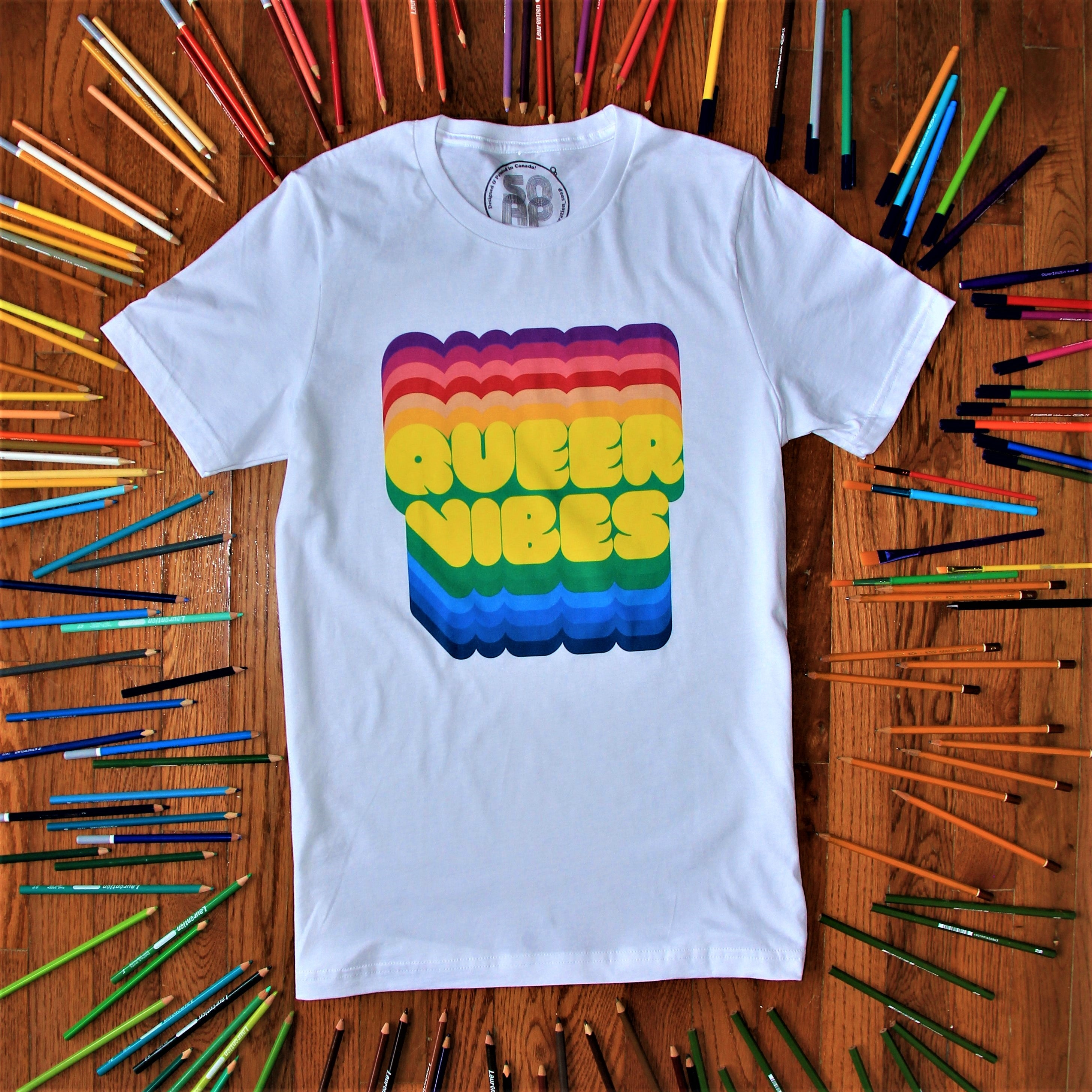 QUEER VIBES - white t-shirt with yellow text with rainbow borders reading 'QUEER VIBES'