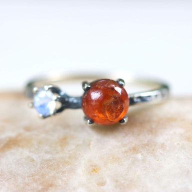 Round Sunstone ring in silver bezel and prongs setting moonstone on the side - by Metal Studio Jewelry