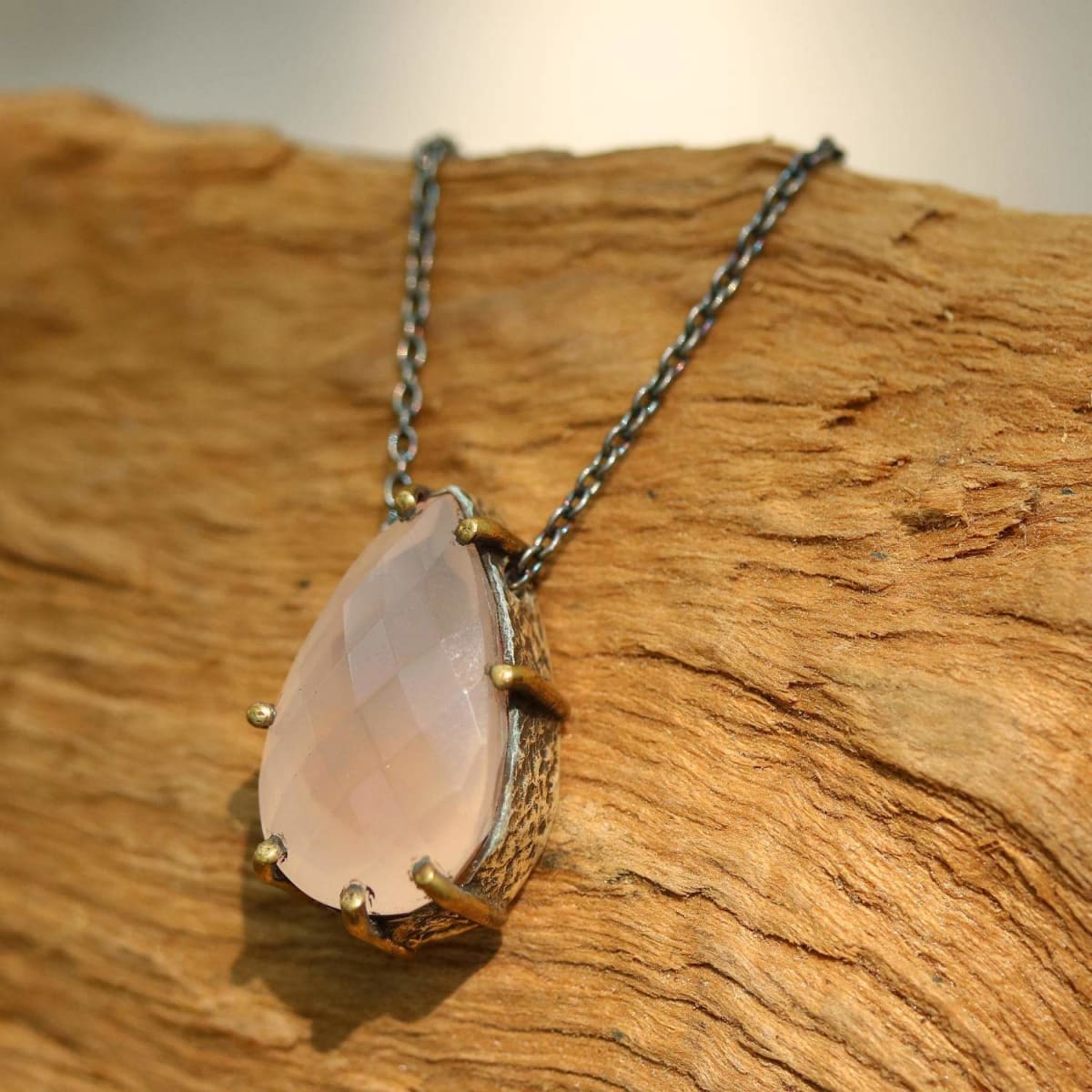 Silver pendant necklace with faceted rose quartz in silver bezel setting featuring polished brass prongs - by Metal Studio Jewelry