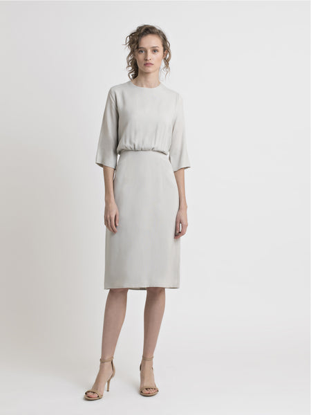 Female model wearing a sand color knee length blouson dress with 3/4 sleeve from the RÉZO women's collection